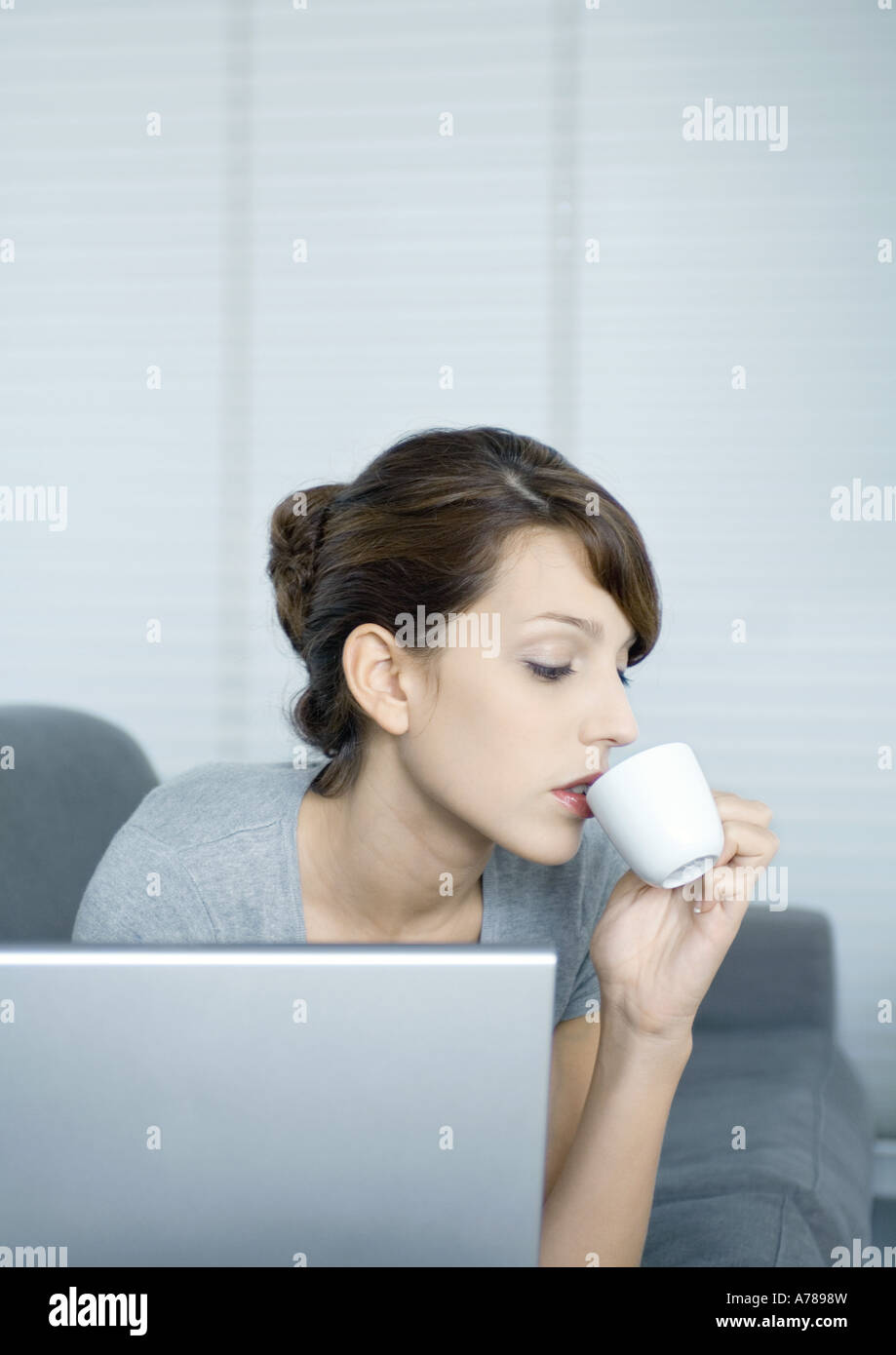 Young woman on couch, using laptop and drinking coffee - Stock Image