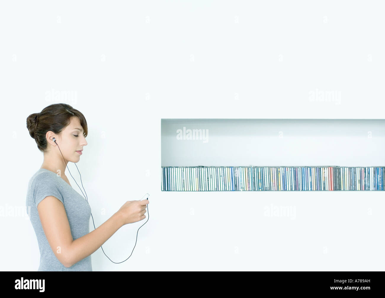 Young woman standing, listening to MP3 player, next to row of CDs, eyes closed - Stock Image