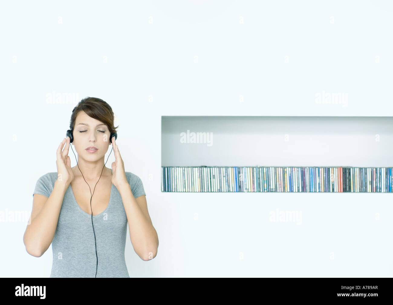 Young woman standing, listening to headphones, next to row of CDs, eyes closed - Stock Image