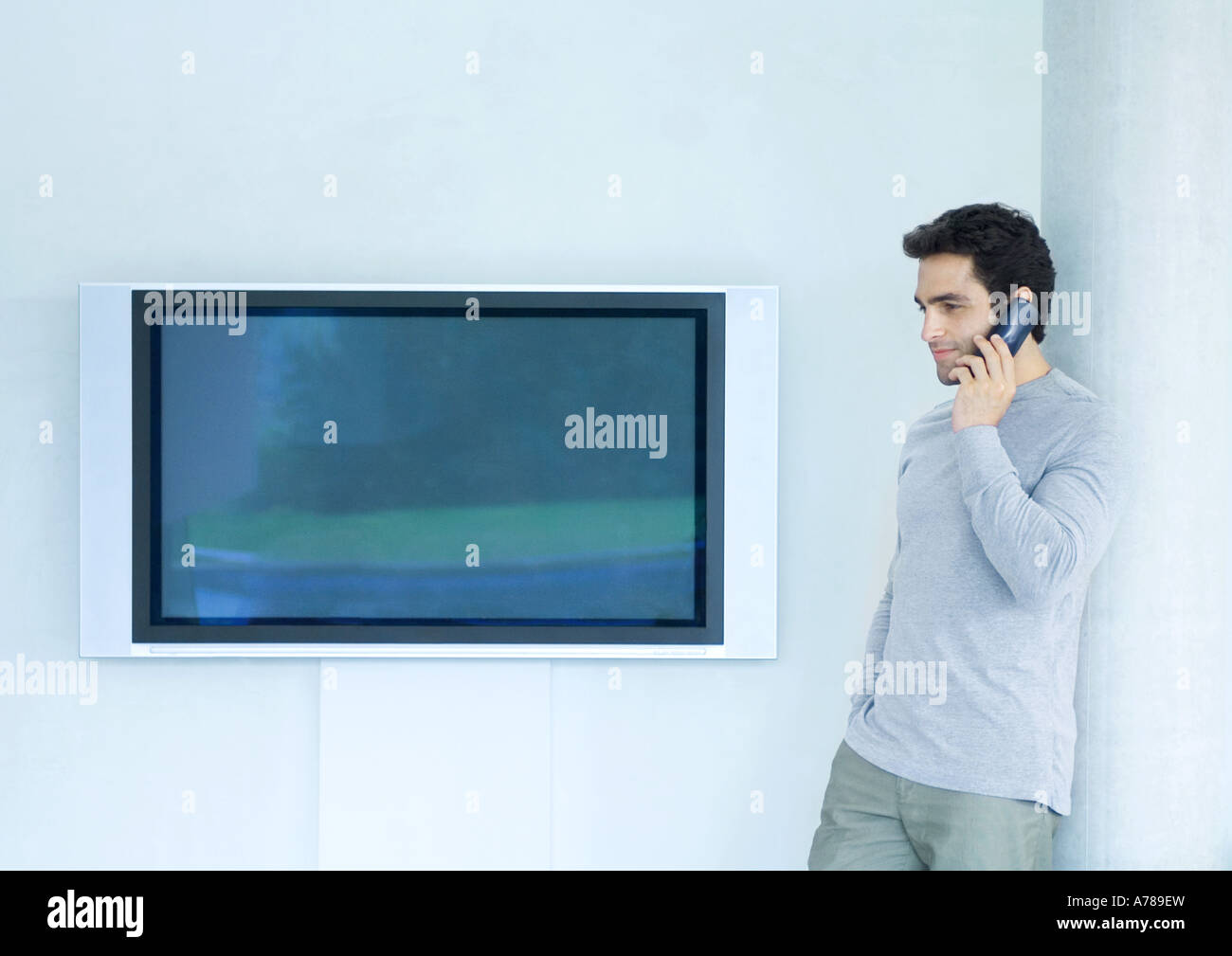 Man leaning against wall using phone, next to widescreen TV - Stock Image