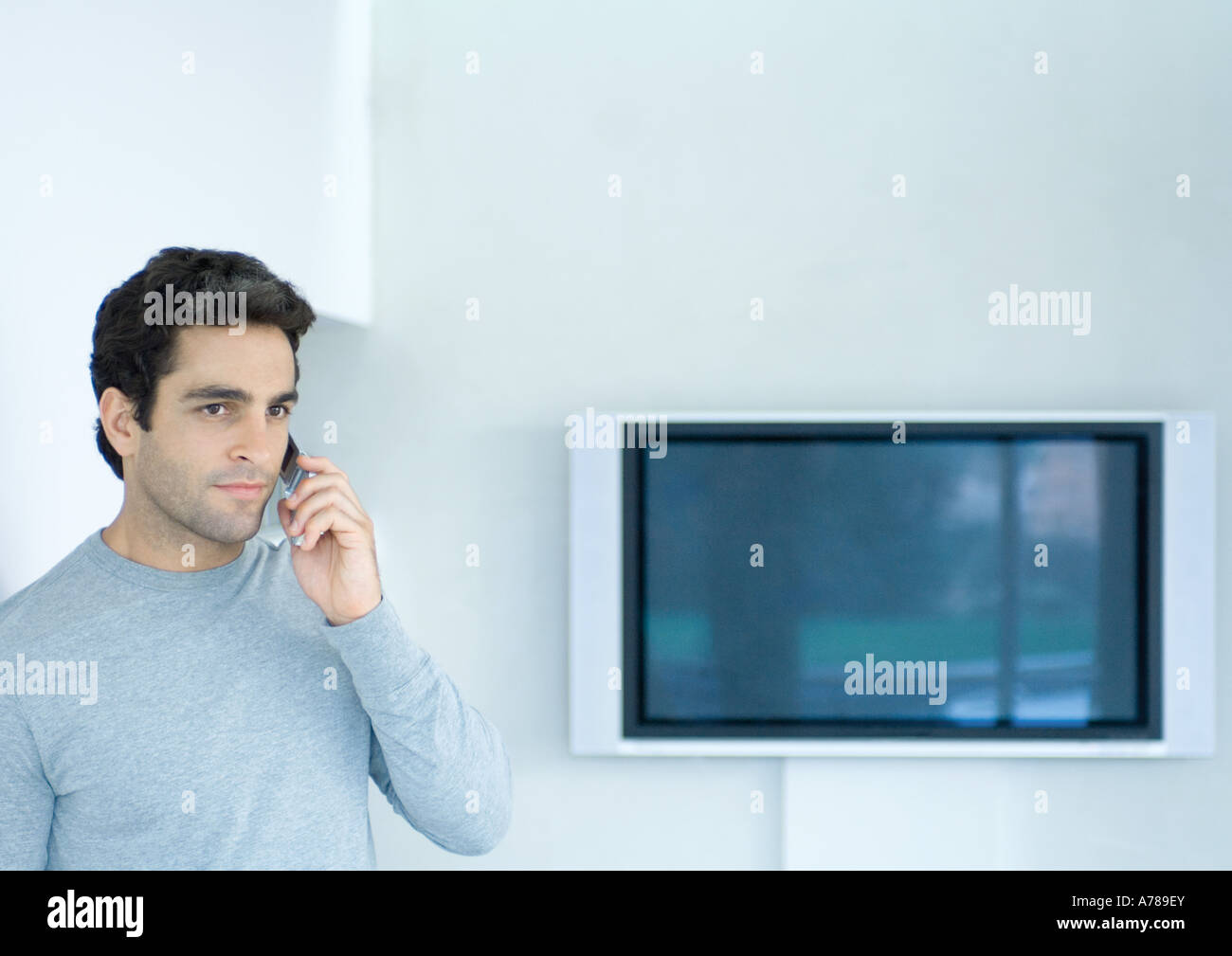 Man using phone, widescreen TV in background - Stock Image