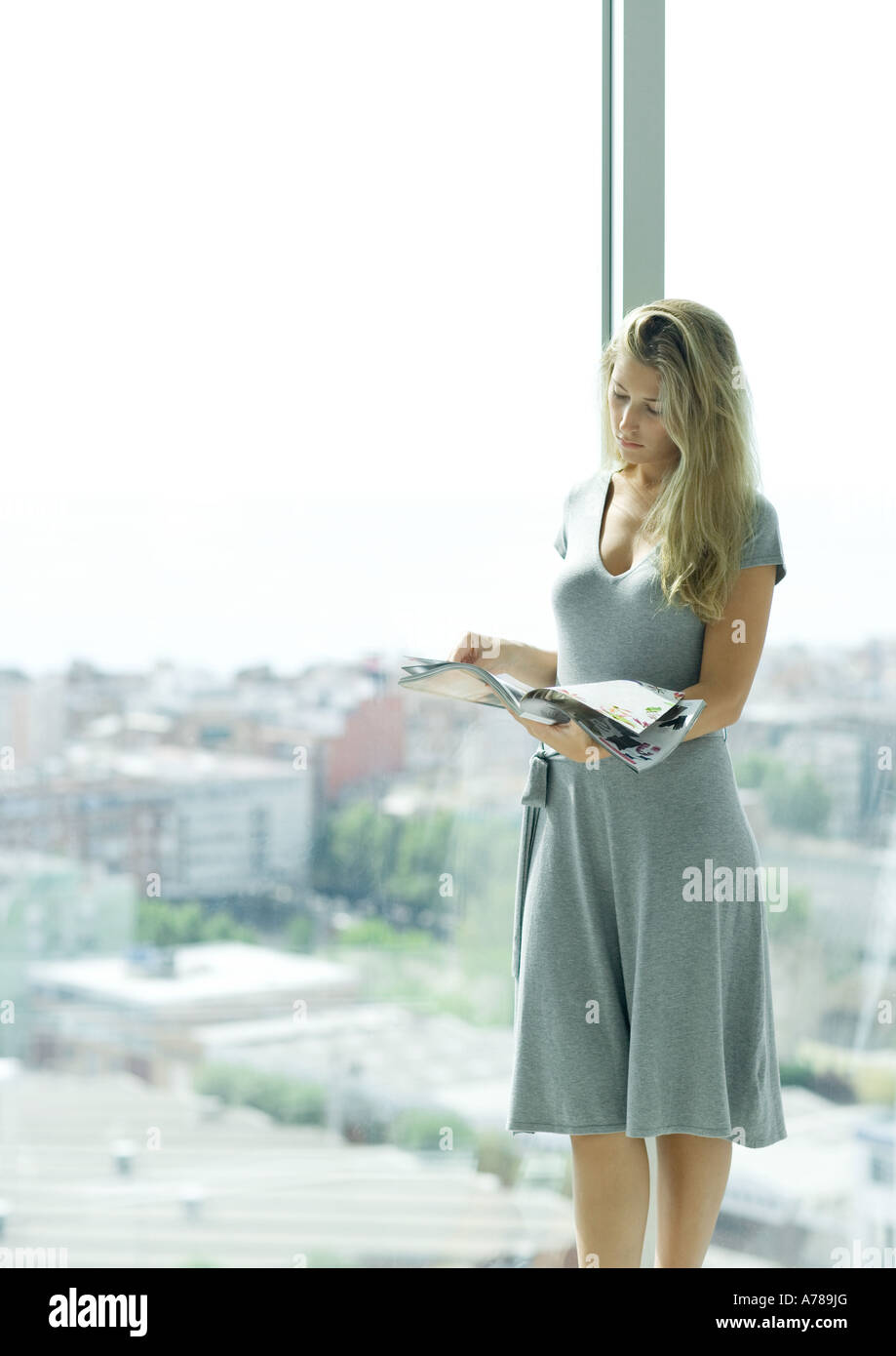 Young woman standing by window, looking at magazine - Stock Image