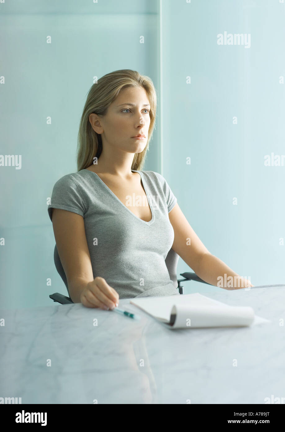 Woman sitting at table with pad of paper, pen and bottle of water, looking down - Stock Image