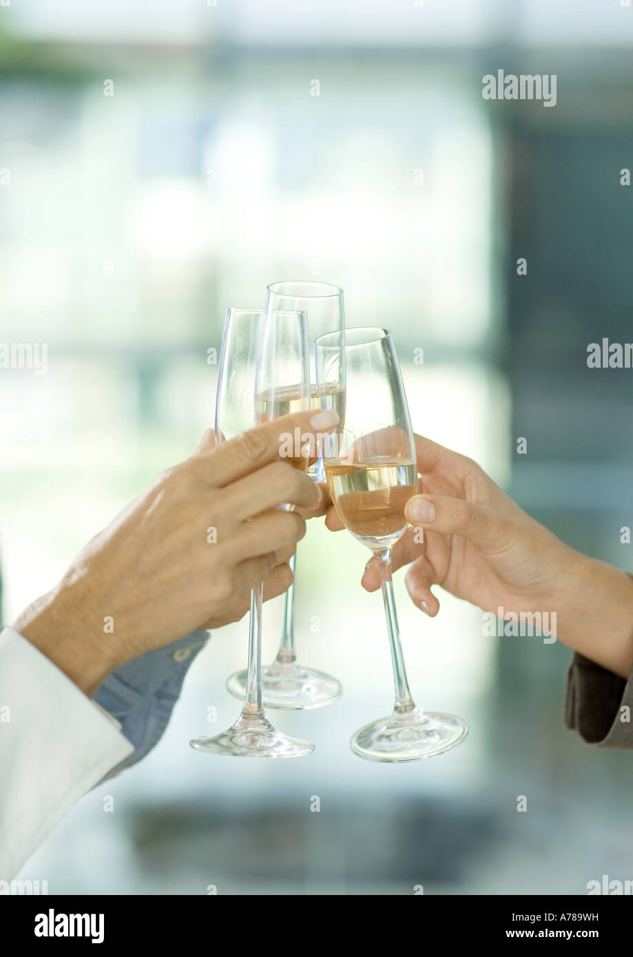 Toasting with glasses of champagne, cropped view of hands - Stock Image