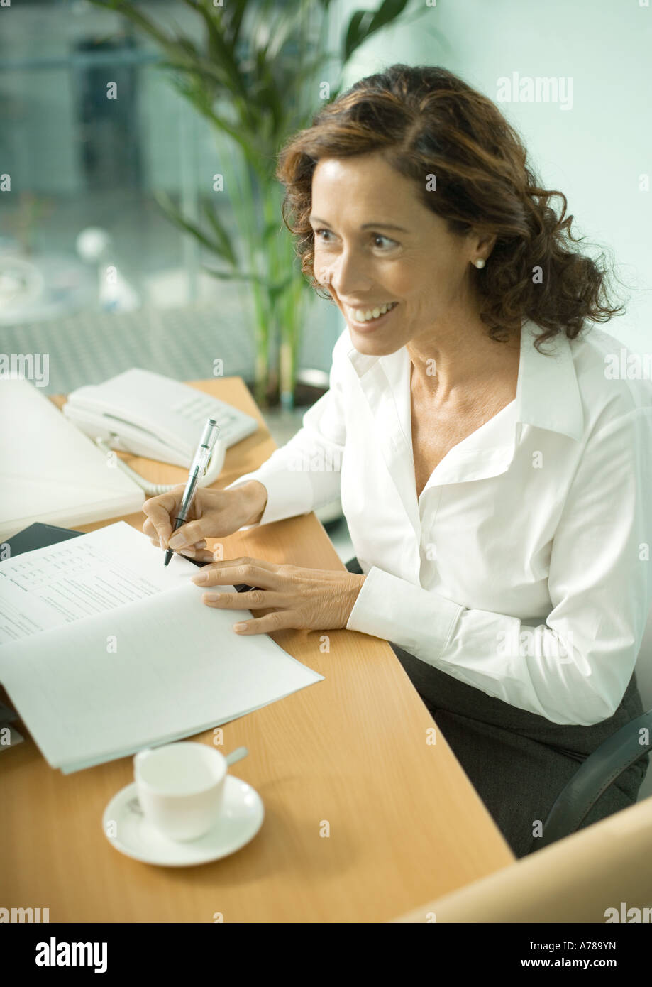Mature professional woman sitting at table, smiling and looking out of frame - Stock Image