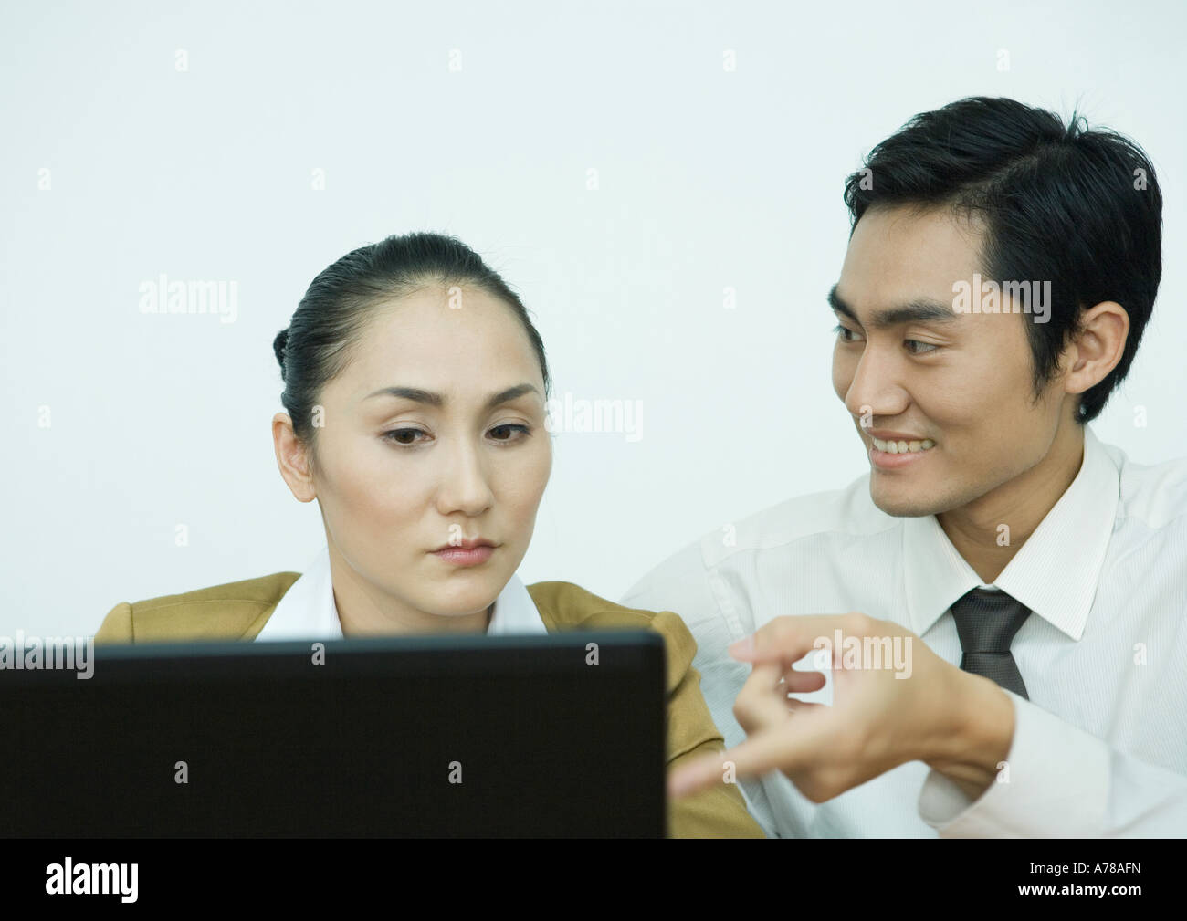 Two business associates using computer, man pointing toward screen - Stock Image