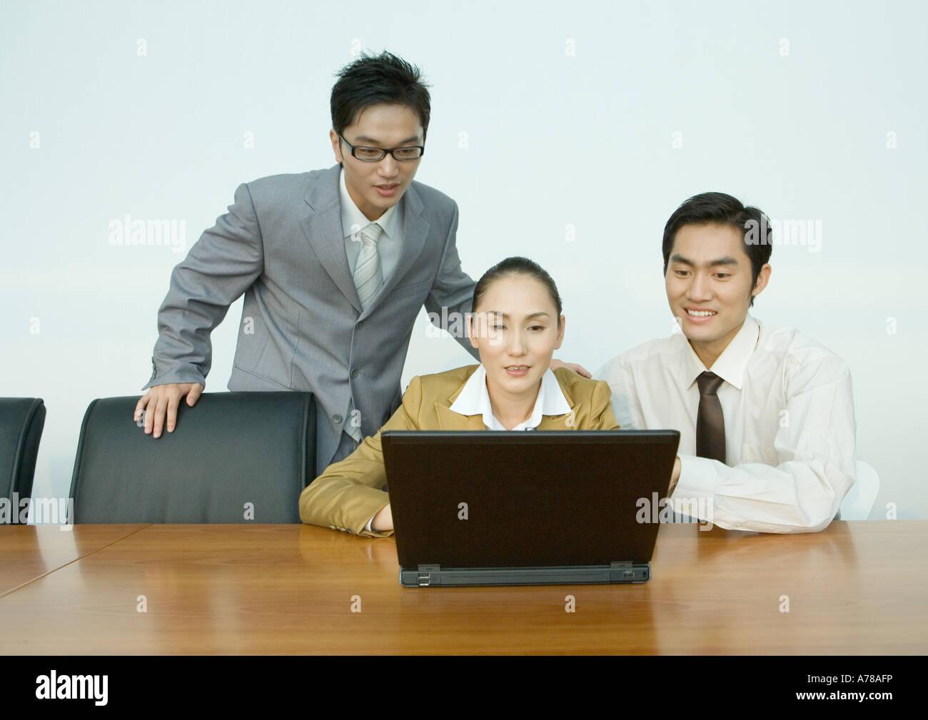 Three business associates using laptop - Stock Image