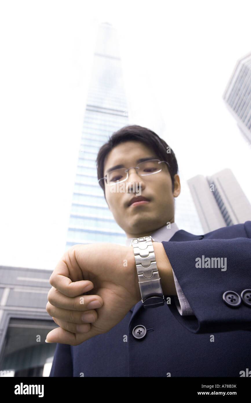 Businessman standing checking time on wristwatch, skyscraper in background - Stock Image
