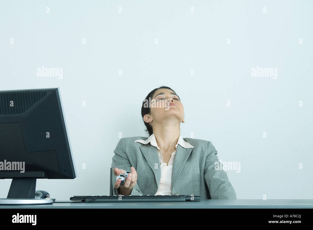 Businesswoman holding yinyang balls, sitting at desk, head back and eyes closed - Stock Image