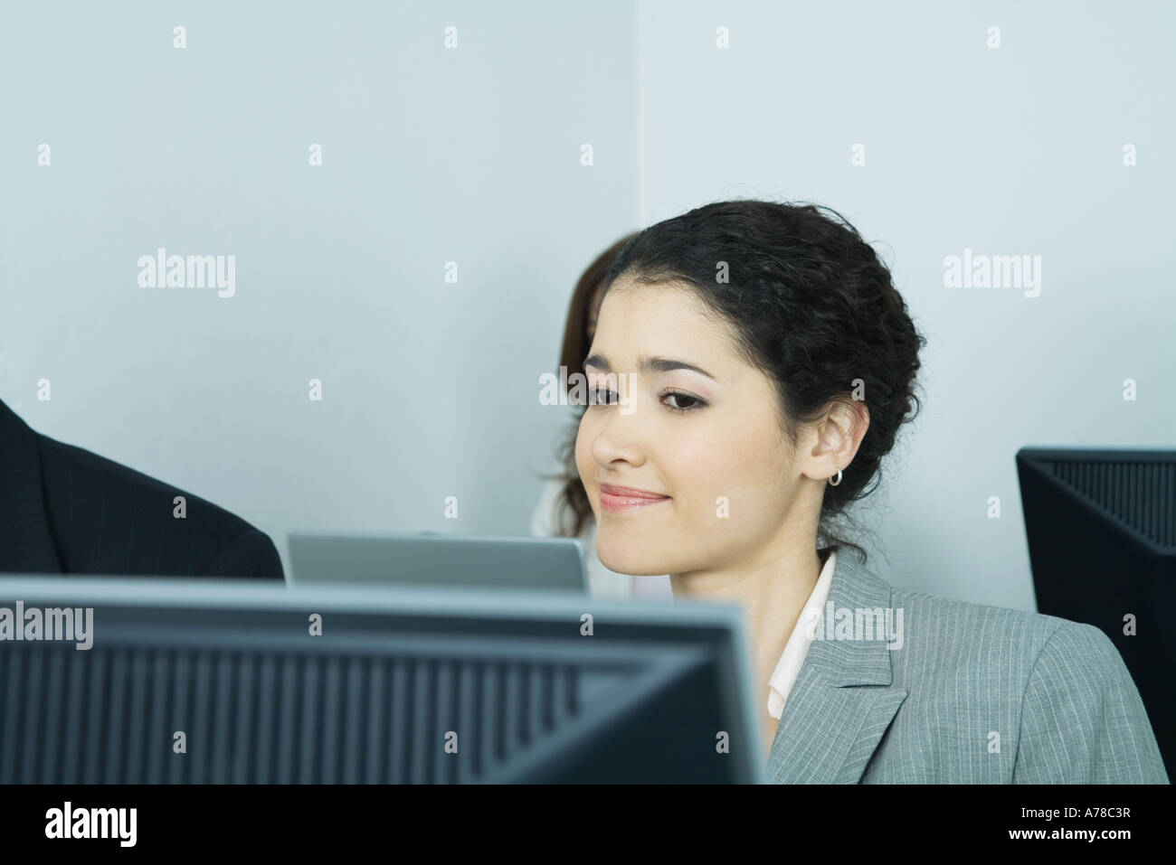 Businesswoman sitting at computer, smiling - Stock Image