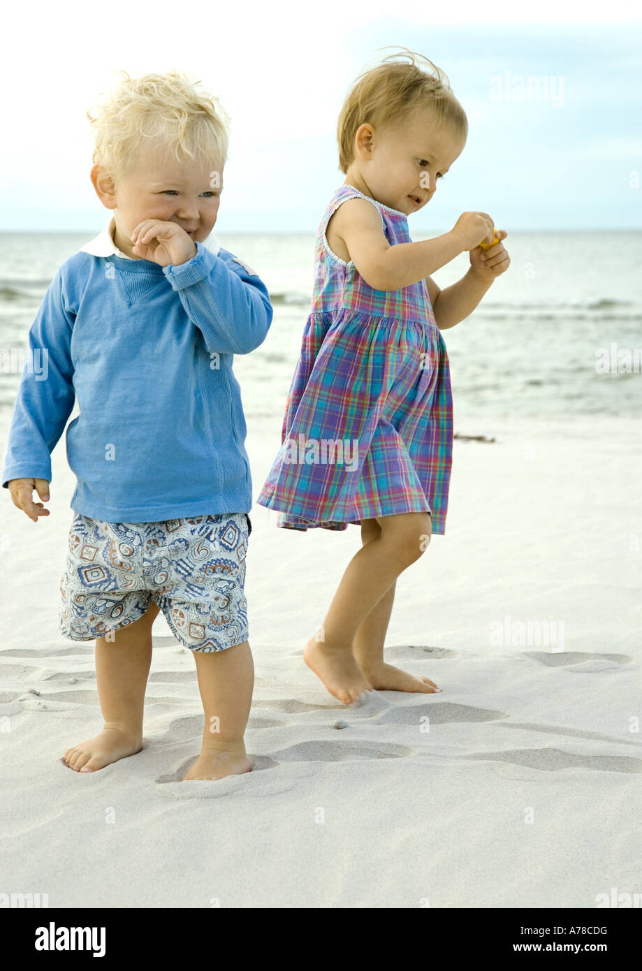 Two toddlers standing on beach - Stock Image
