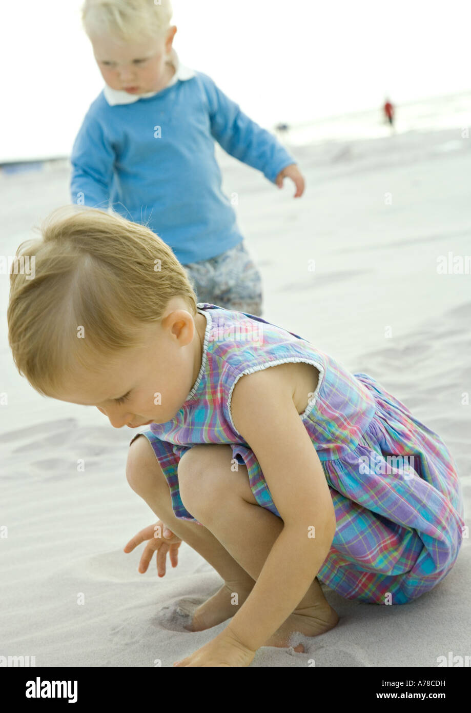 Two toddlers playing on beach - Stock Image