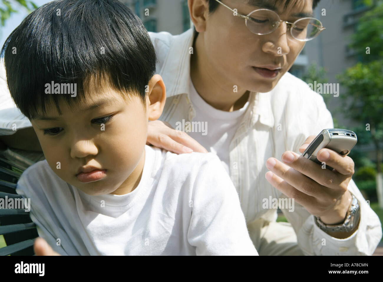 Man looking at cell phone while son looks away, frowning - Stock Image
