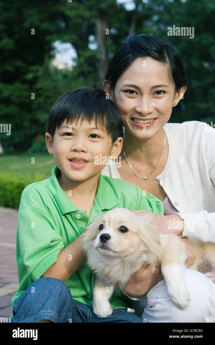 Boy with mother and pet dog, portrait - Stock Image