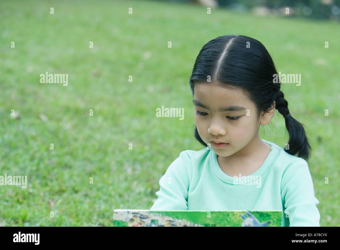 Little girl reading book - Stock Image