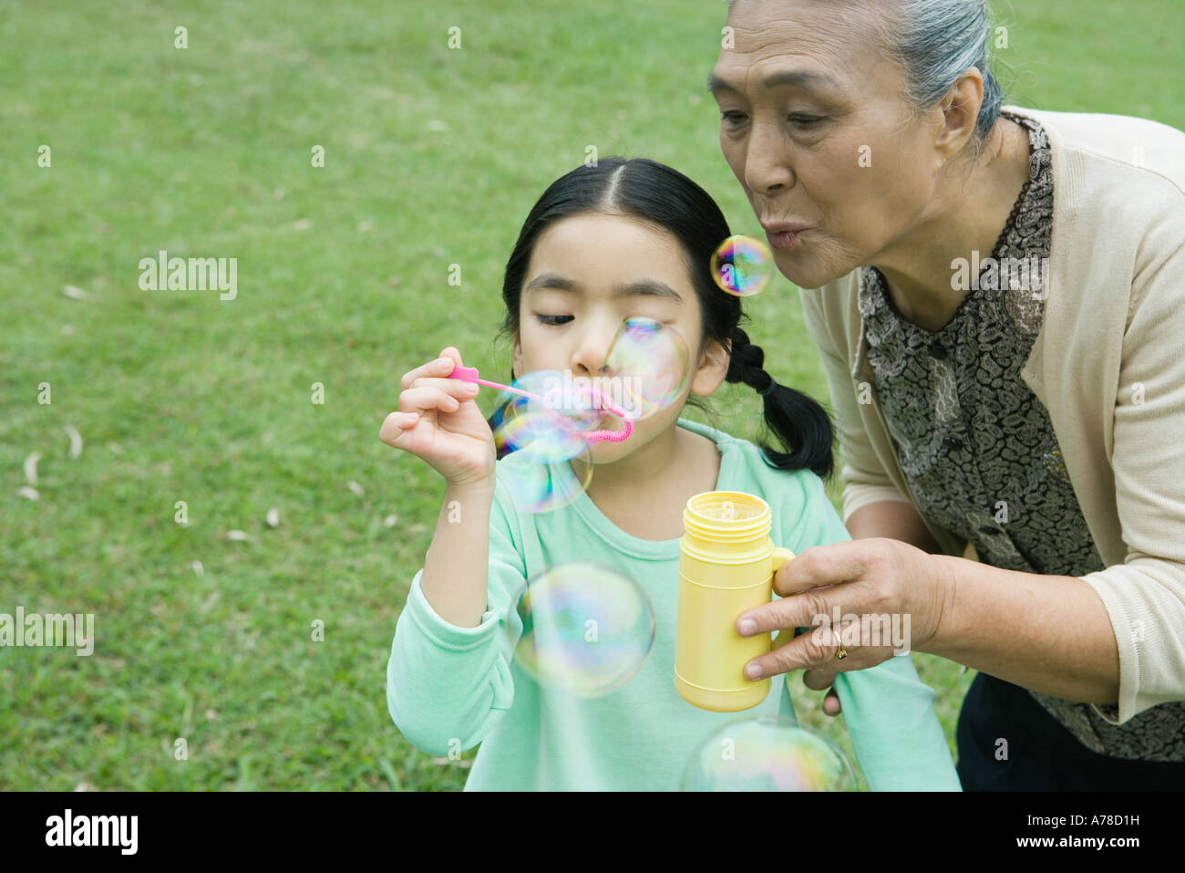 Little girl and grandmother blowing bubbles Stock Photo