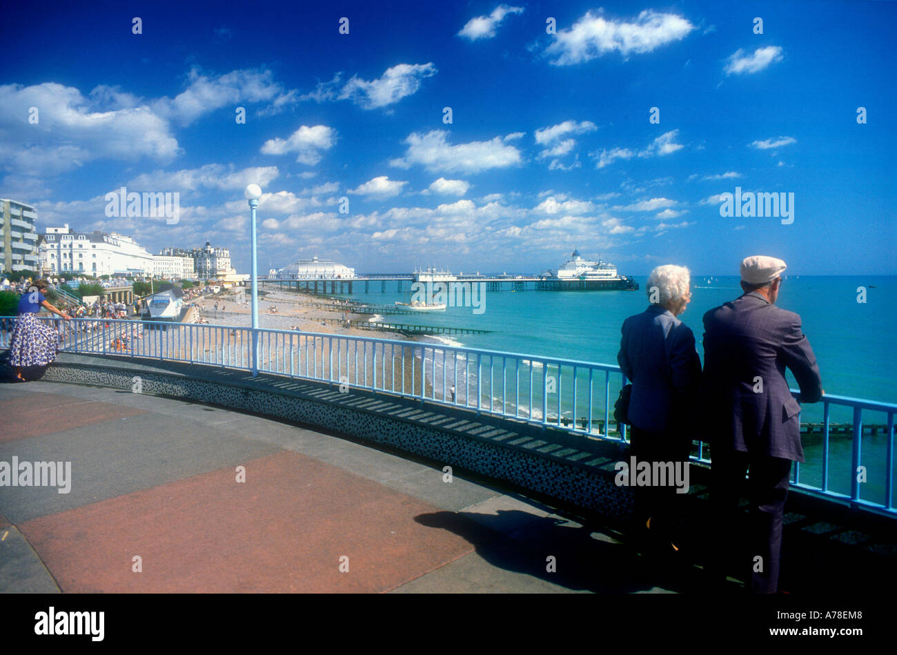 Two elderly people staring out to sea from the promenade at Eastbourne Sussex UK Stock Photo