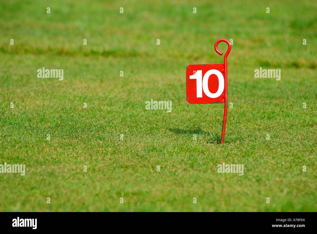 number 10 painted on red metal golf flag - Stock Image