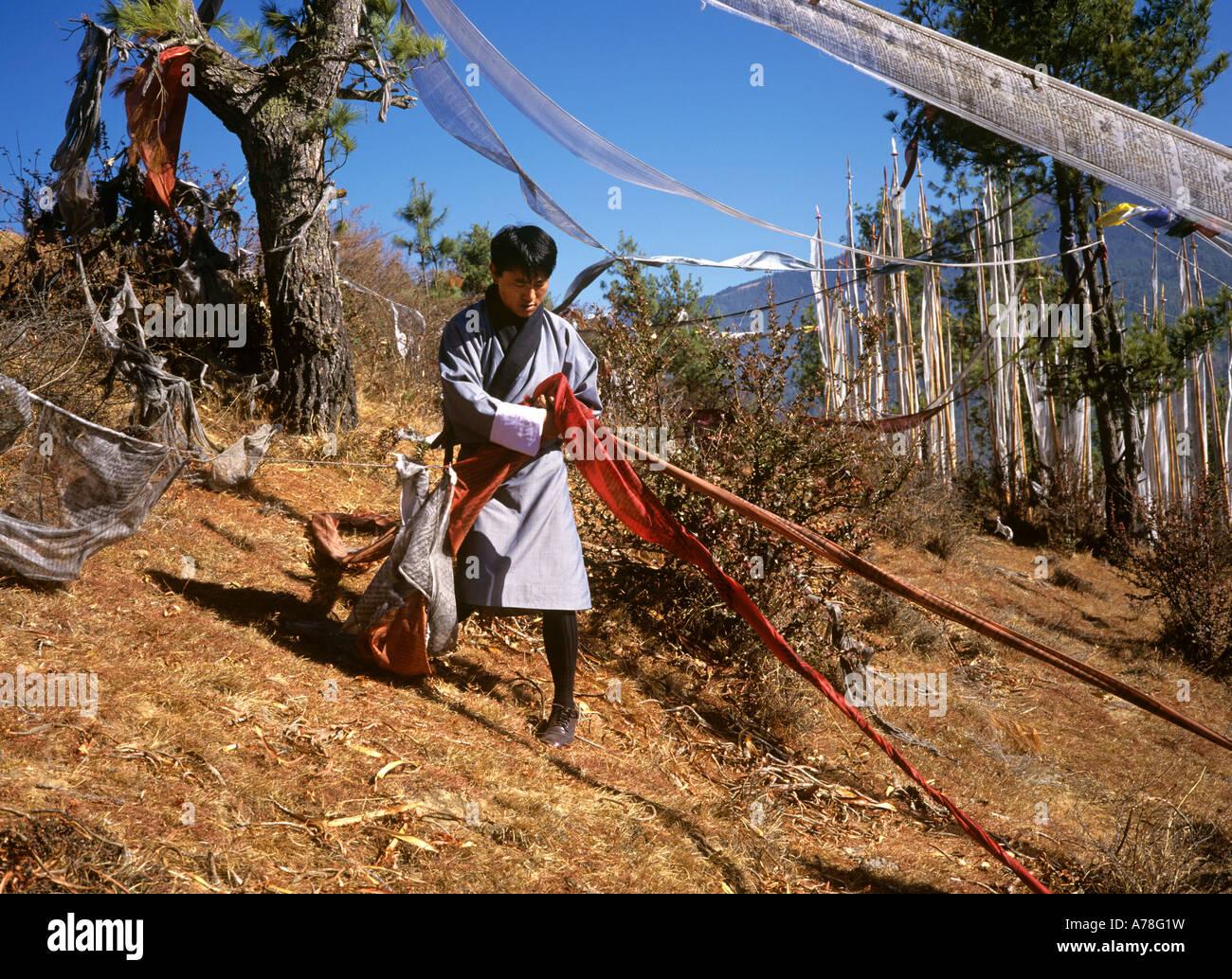 Bhutan Thimpu man tying up prayer flags at Motithang - Stock Image