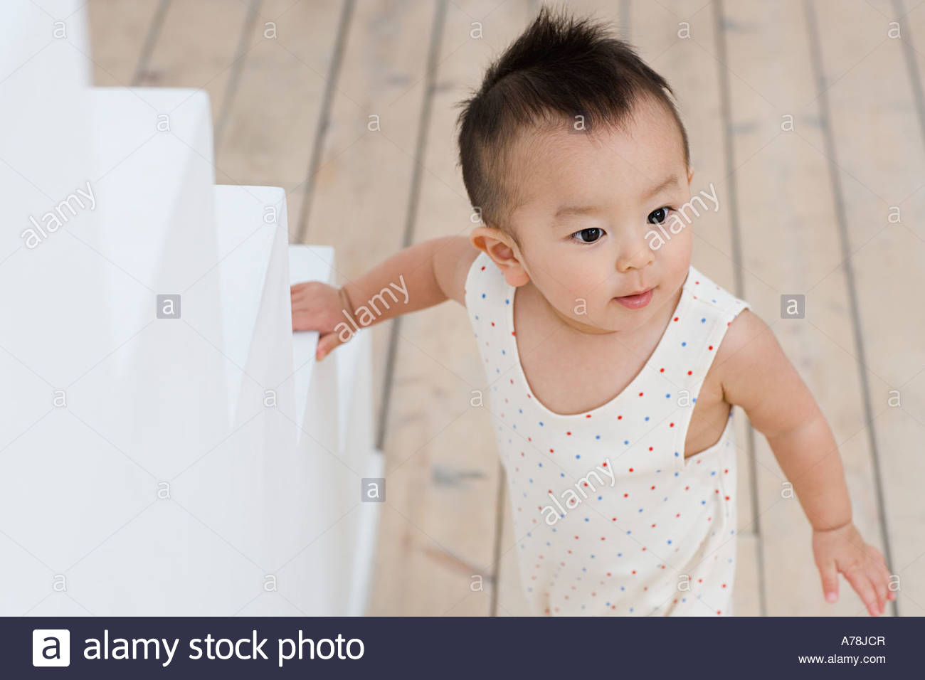 Baby standing near steps - Stock Image