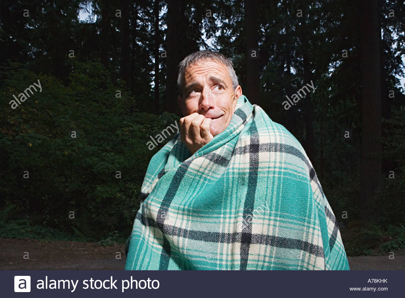 Scared man in a forest - Stock Image