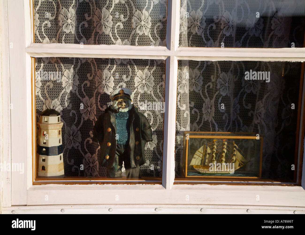 Window decorated with maritime motifs A lighthouse an old sailor and a model of a sail ship - Stock Image