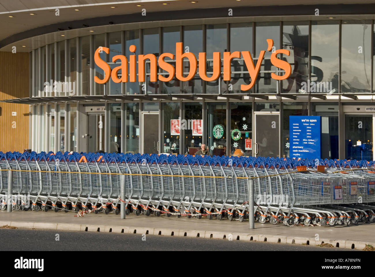 London large stack of Sainsburys supermarket trolleys in front of store entrance includes - Stock Image