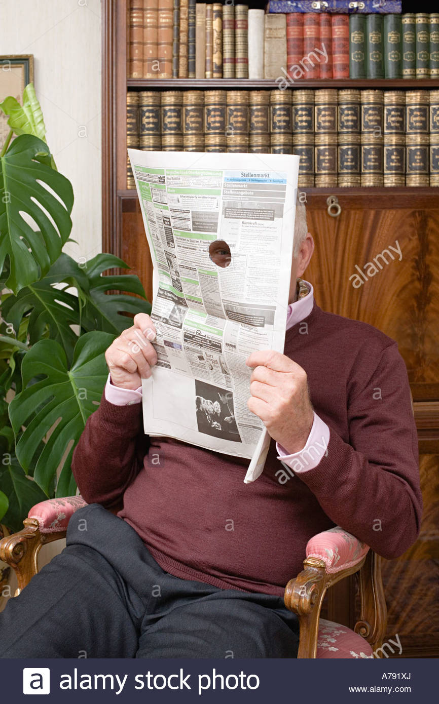 Senior man looking through a hole in a newspaper - Stock Image