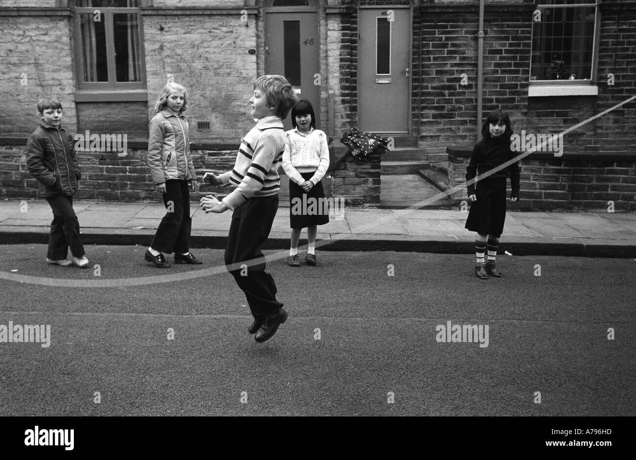 Children kids playing together skipping in the street Saltaire Bradford Yorkshire UK  1981 HOMER SYKES - Stock Image