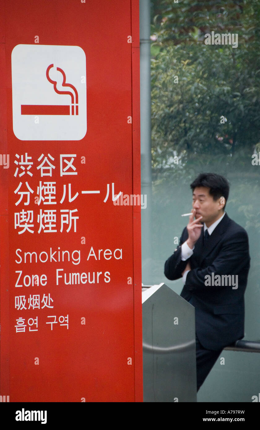 A Japanese man in a designated smoking area Tokyo Japan - Stock Image