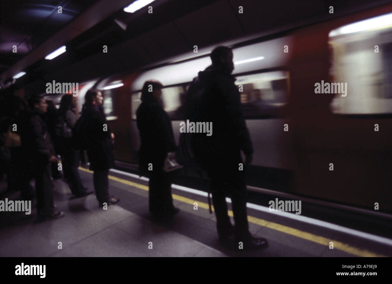 Commuters in London Underground Station waiting by moving train - Stock Image