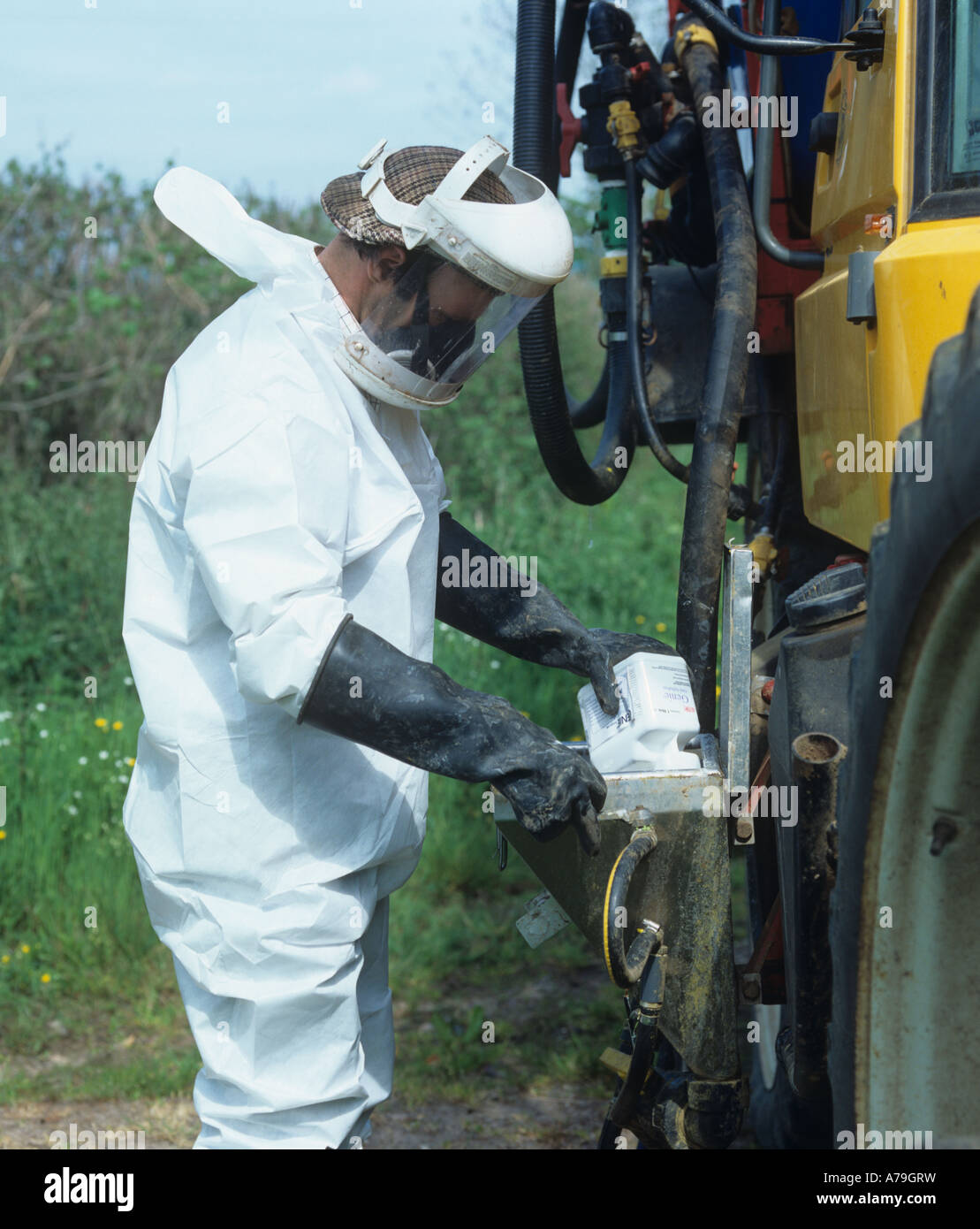 Tractor driver in full protective clothing adding chemical to the spray tank of a crop sprayer - Stock Image