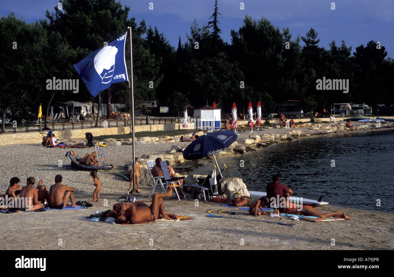 Tourists tanning in the late afternoon sunshine at a Blue Flag beach, Istrian Peninsula, Croatia - Stock Image
