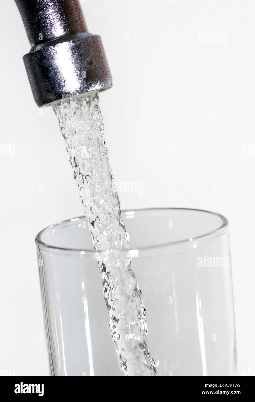 fresh water running from tap faucet into glass - Stock Image