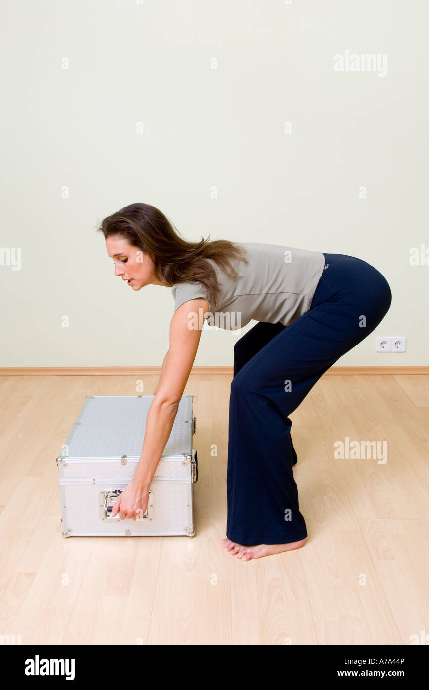 young woman lifting a metal case, correct posture, gentle stooping - Stock Image