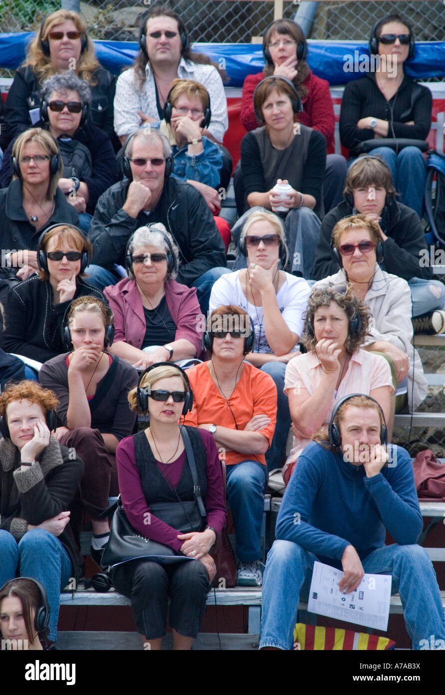 The audience at an open air theatre experience listening intently through wearing headphones - Stock Image