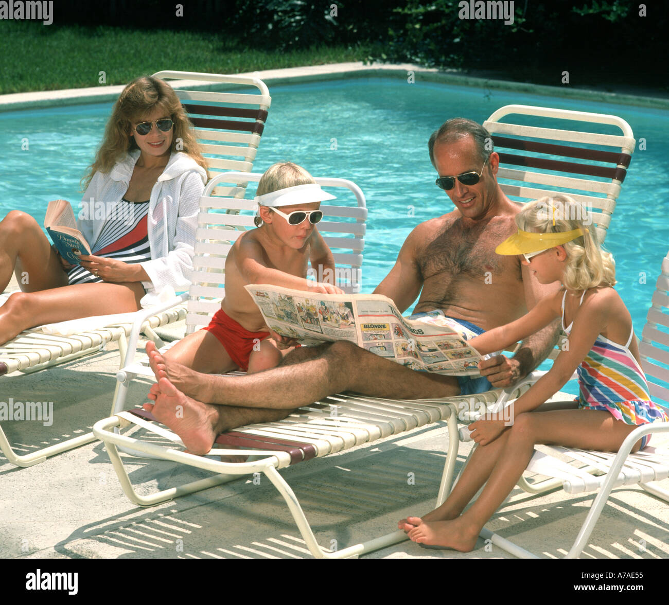 family of four relaxing and reading comics by swimming pool - Stock Image