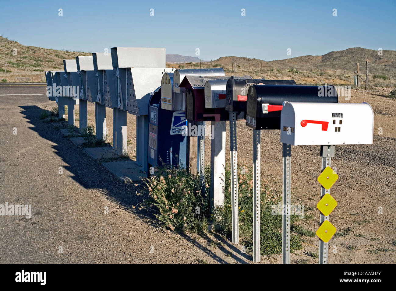 Row of mailboxes off a rural road in west Texas - Stock Image