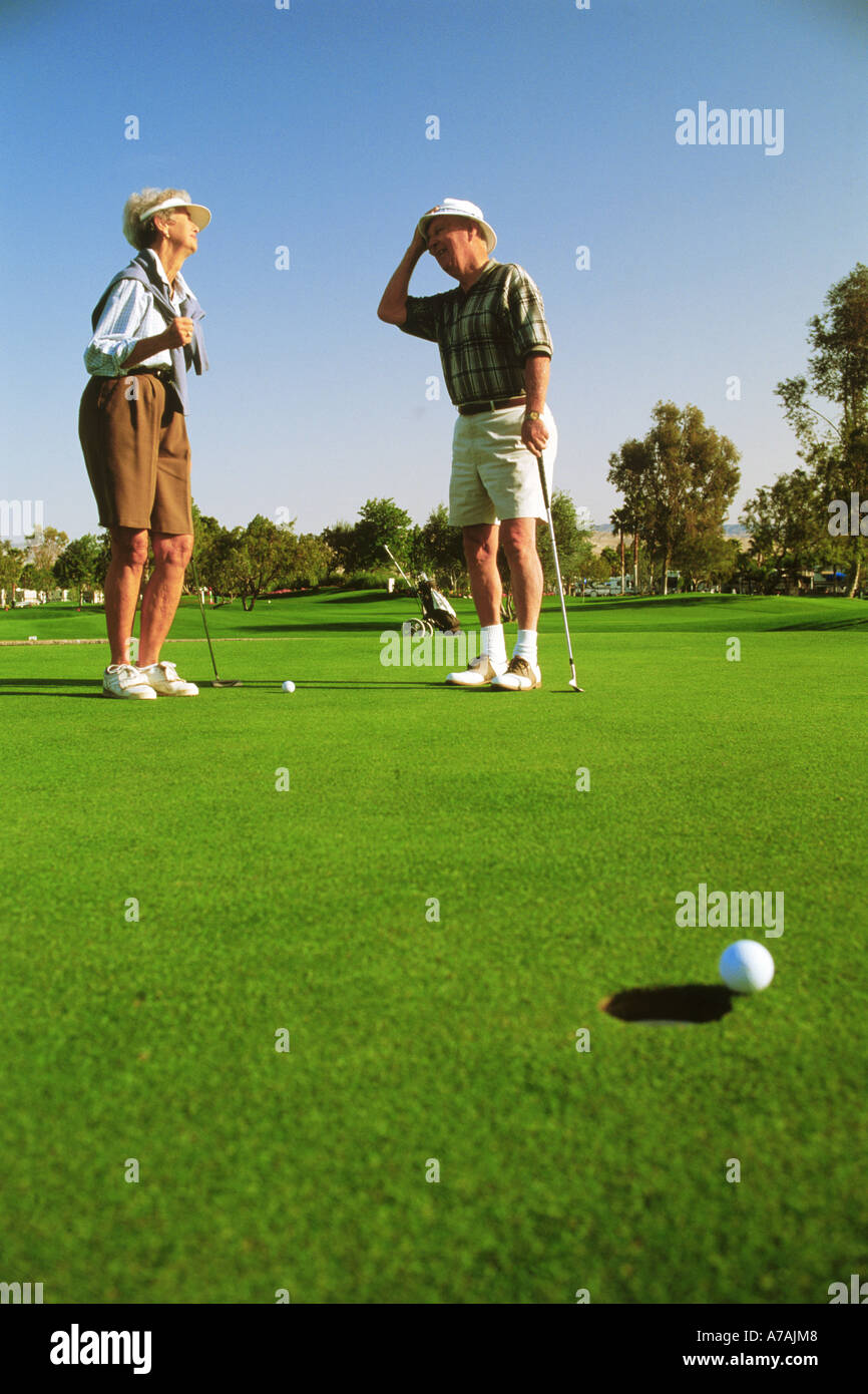 Couple in their 70s just missing putt while playing golf in Palm Springs, California - Stock Image