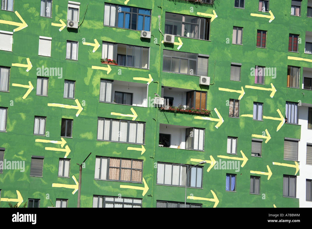 apartment building in Tirana, Albania with green walls and painted arrows - Stock Image