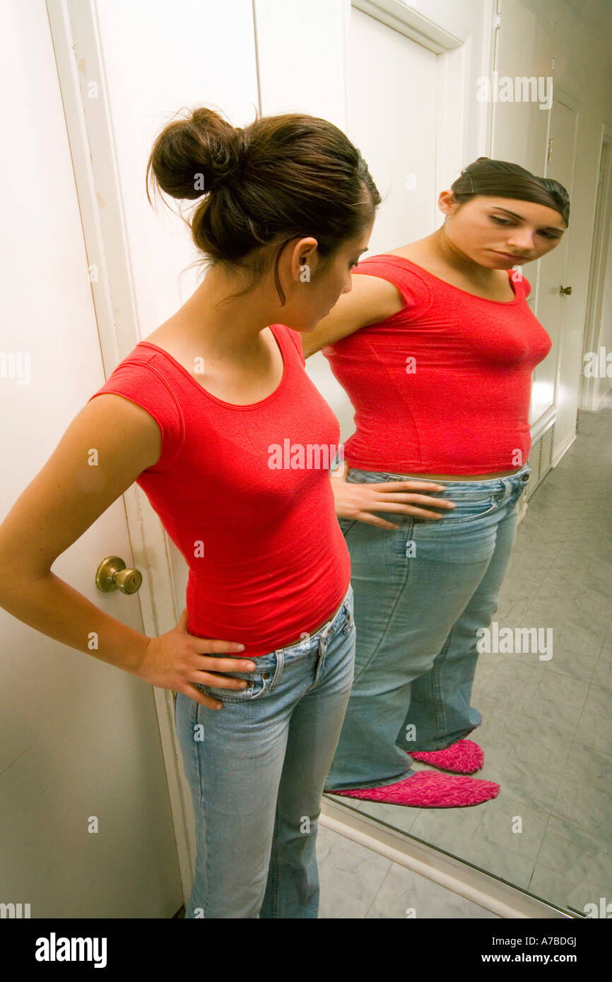Hispanic teen girl sees herself as overweight in reflection in mirror Model released - Stock Image