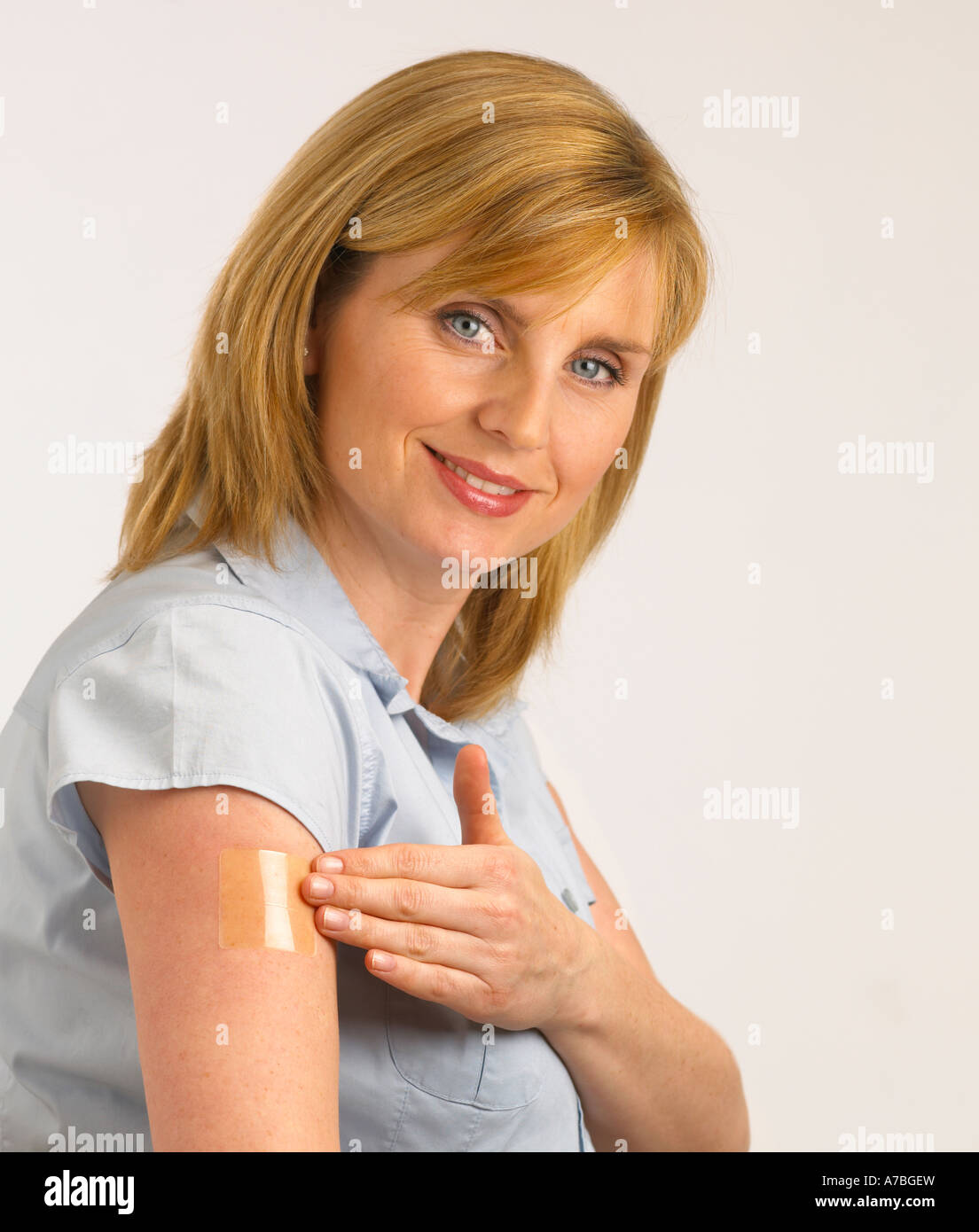 ATTRACTIVE HEALTHY YOUNG BLONDE WOMAN APPLYING TRANSPARENT NICOTINE PATCH TO ARM - Stock Image