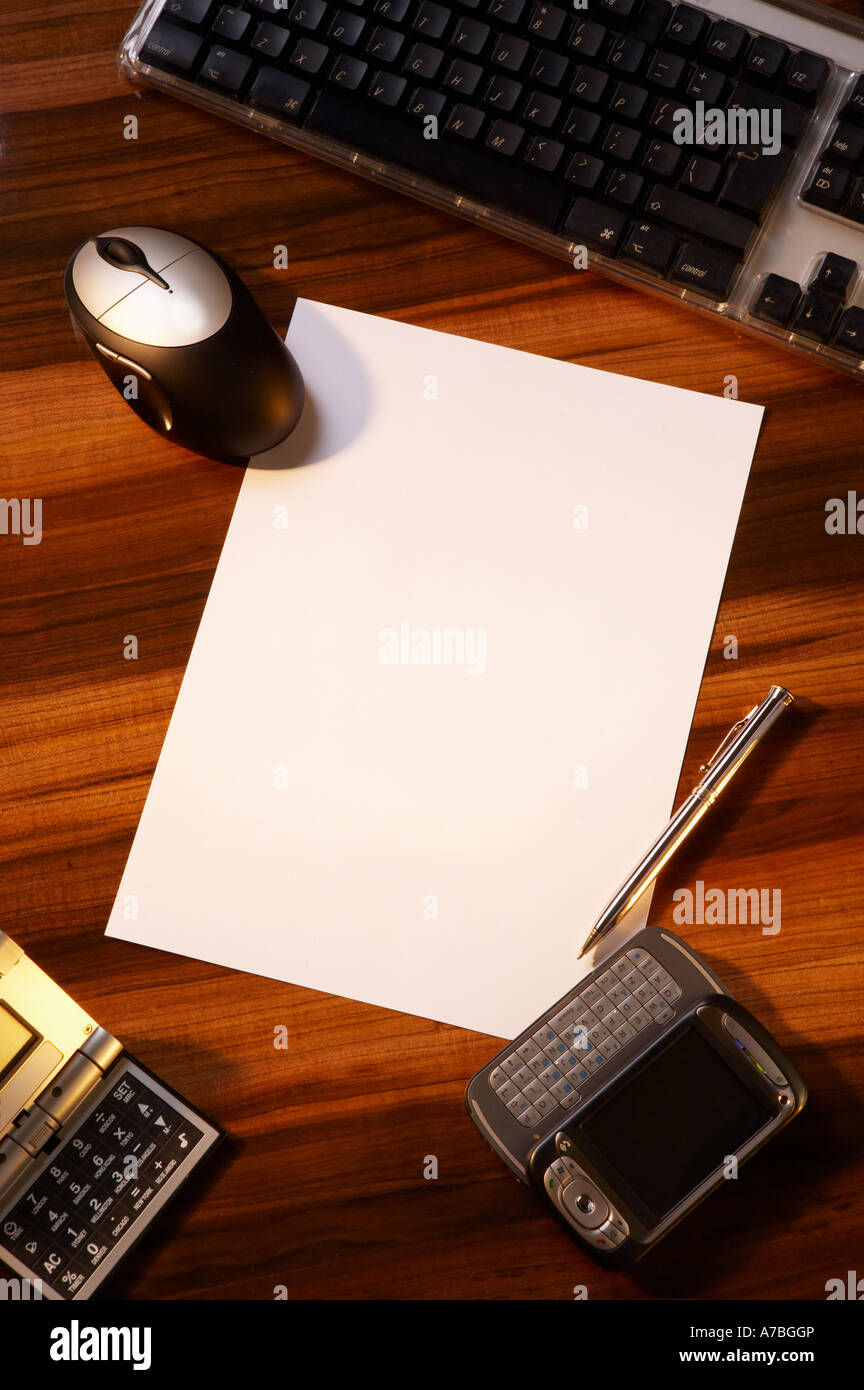 POLISHED WOOD EXECUTIVE DESK WITH COMPUTER KEYBOARD PDA PHONE CALCULATOR PAPERS AND PEN - Stock Image