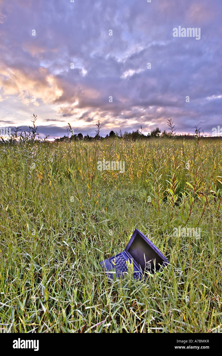 Discarded laptop in field of long grass - Stock Image