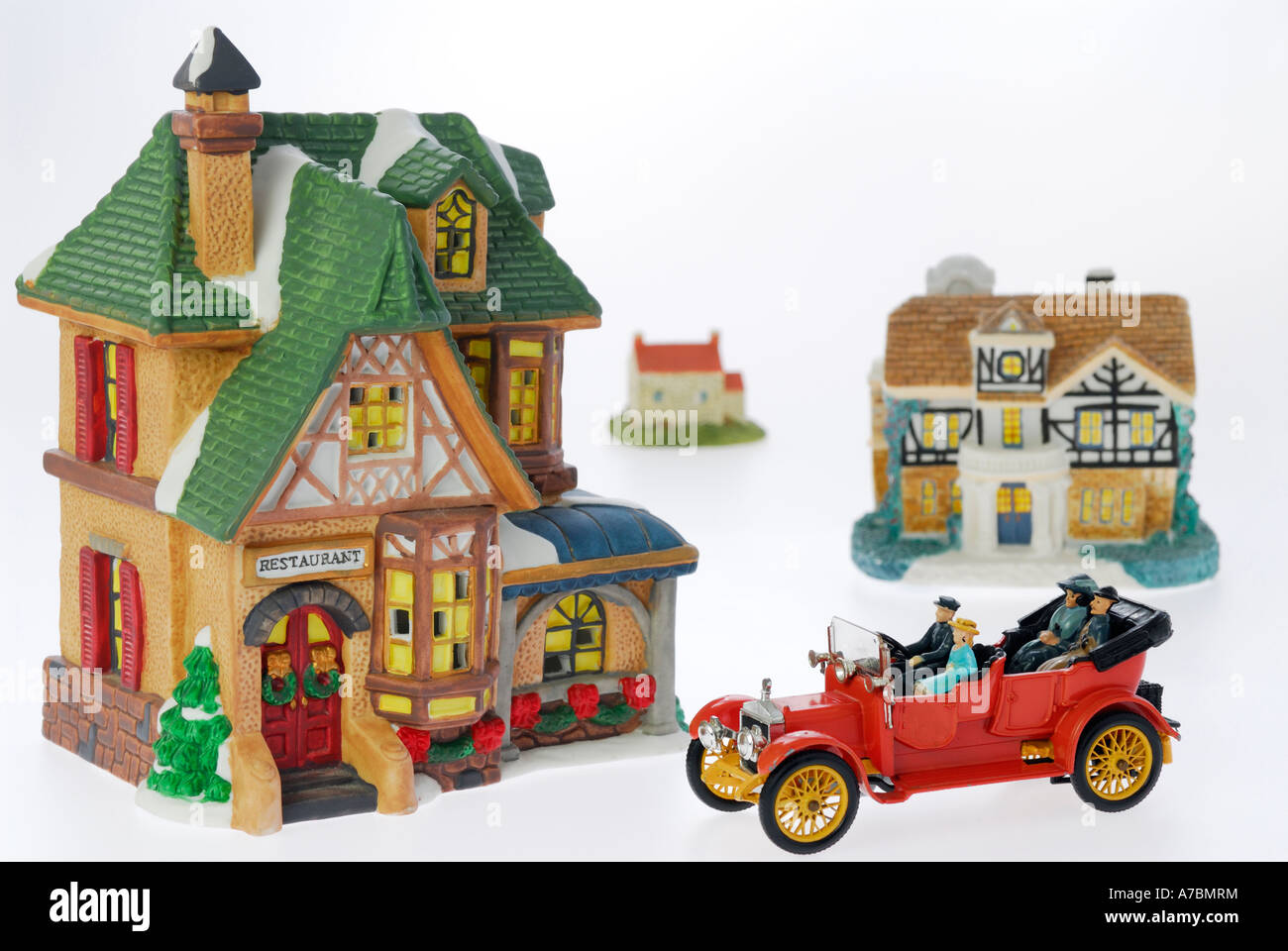 Model toy houses and car of a rich family going out to a restaurant on white background - Stock Image