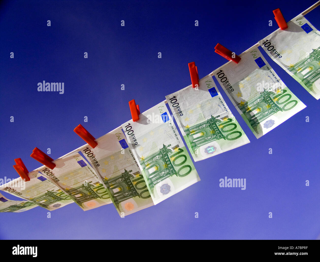 Crisp new Euro notes pegged flying high in a line against a sunny blue sky - Stock Image