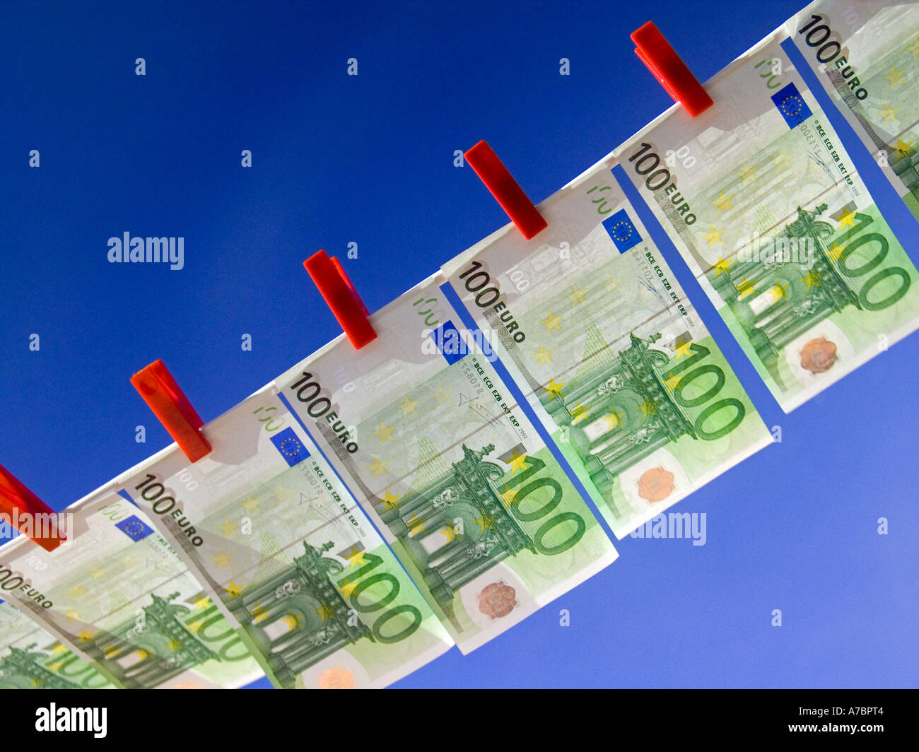 Crisp new 100 Euro notes pegged on a washing line against a sunny blue sky Horizontal Landscape Outdoors Exterior - Stock Image