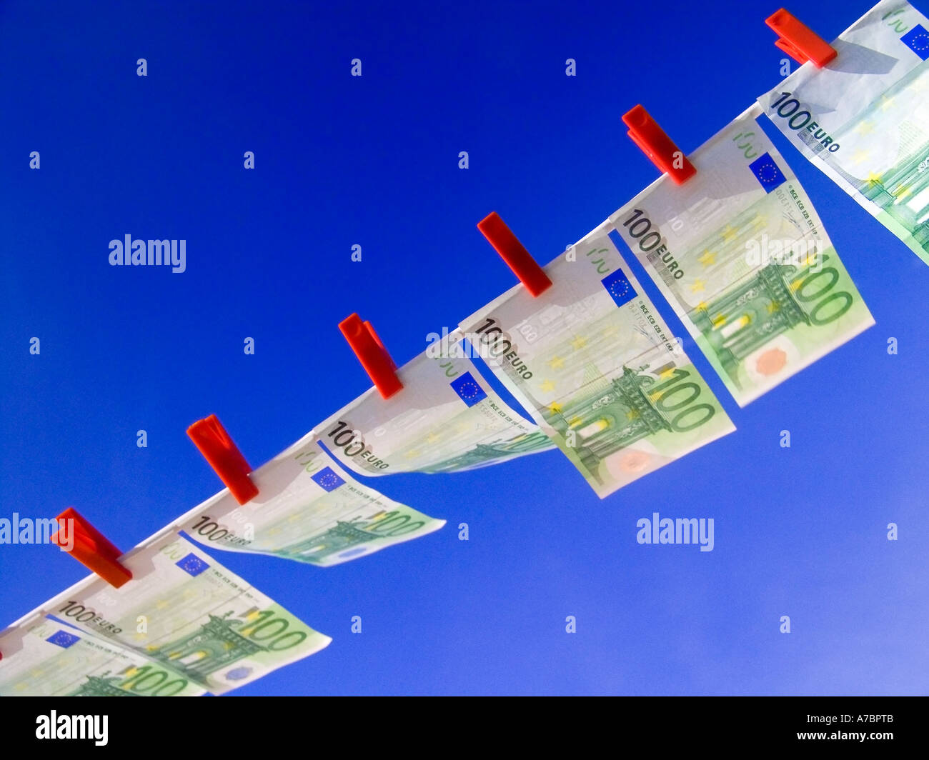 Crisp new 100 Euro notes fluttering flying high in the breeze pegged in a line against a sunny blue sky Horizontal Landscape - Stock Image