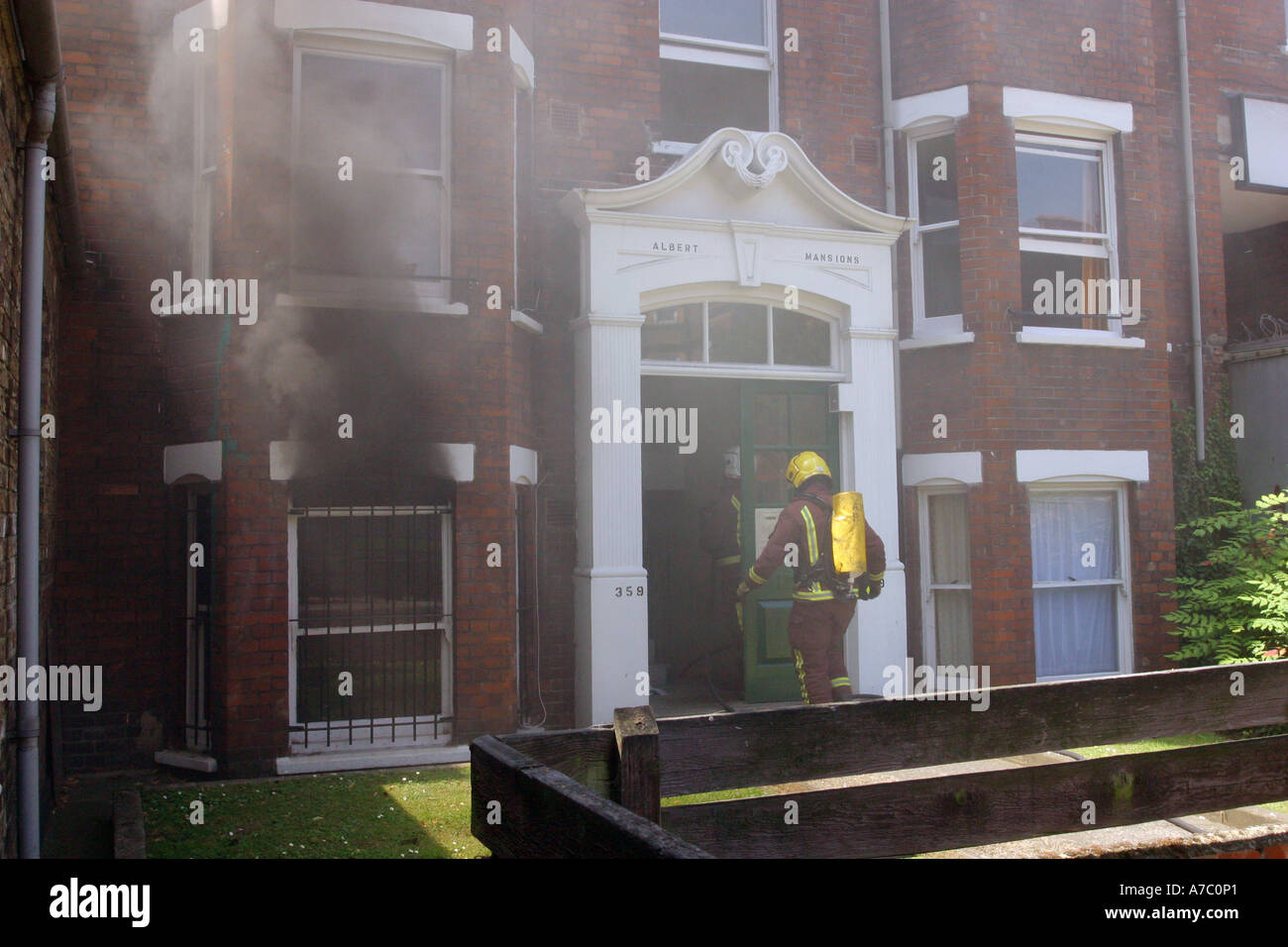 Firefighters putting out fire in basement council flat - Stock Image