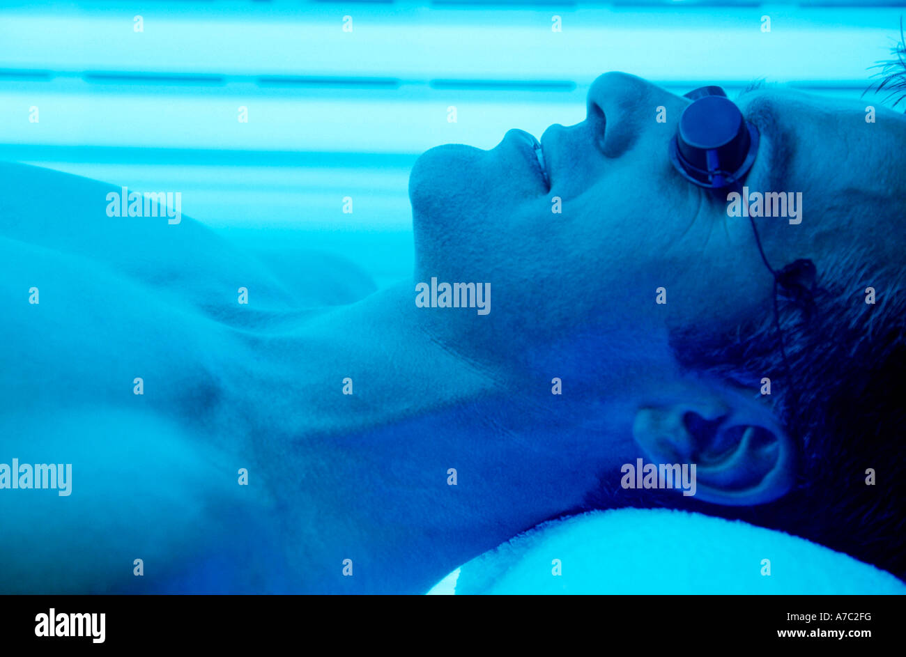 Man lying on a sunbed - Stock Image